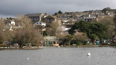 Helston from the ornamental lake (© Tony Atkin [CC BY-SA 2.0 (https://creativecommons.org/licenses/by-sa/2.0)], via Wikimedia Commons (original photo: https://commons.wikimedia.org/wiki/File:Helston_from_the_ornamental_lake_-_geograph.org.uk_-_124255.jpg))