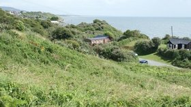 Scattered houses on the coast at Ardamine  (© © Copyright Simon Mortimer (https://www.geograph.ie/profile/12126) and licensed for reuse (http://www.geograph.ie/reuse.php?id=1465993) under this Creative Commons Licence (https://creativecommons.org/licenses/by-sa/2.0/).)