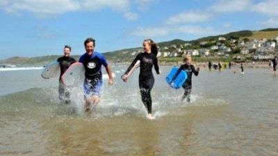 Family Running Beach Boards