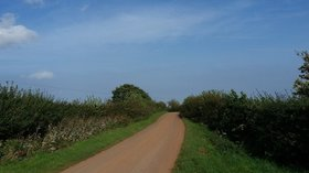 A country lane  (© © Copyright Peter Mackenzie (https://www.geograph.org.uk/profile/33238) and licensed for reuse (https://www.geograph.org.uk/reuse.php?id=5571371) under this Creative Commons Licence (https://creativecommons.org/licenses/by-sa/2.0/).)